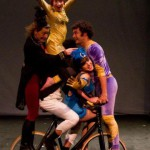 A tower of five circus performers - all balanced on a bike, with a woman in yellow on the top with her arms outstretched