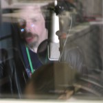 a blurred image taken through glass of Jez singing in a sound booth with a mic in front of him