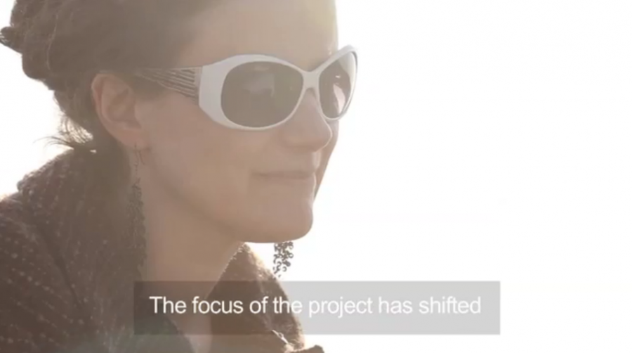 A screen grab of a captioned film. There is a woman's face, shot against the sun, she is wearing long earrings and sunglasses. The text says 'The focus of the project has shifted'