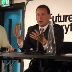 Ed Vaizey, Minster for Culture, Communications and Creative Industries at DCMS sitting at a table speaking animatedly - there is a sign behind him, just readable, which says Future Everything.