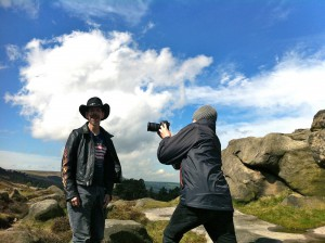 K+Jex Colborne, in a leather jacket and stetson, is being filmed by a camera person against a dramatic backdrop of Yorkshire moors and cloud filled blue sky