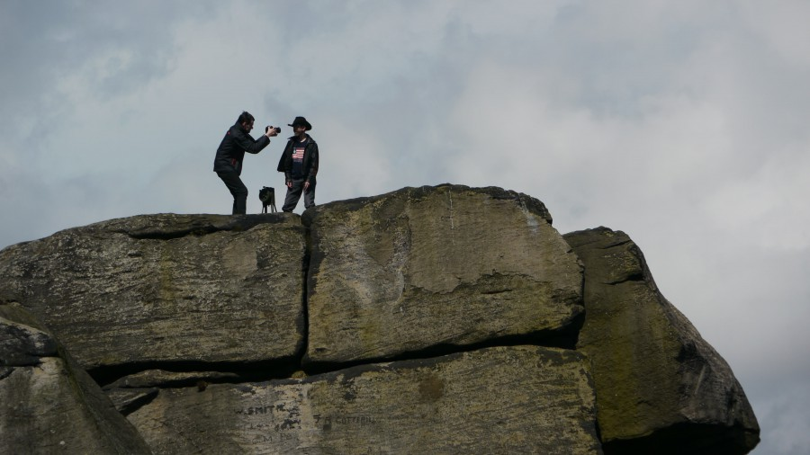 A huge rocky outcrop against a cloudy sky - two figures can be seen - one filming, one in a stetson next to an old air raid siren