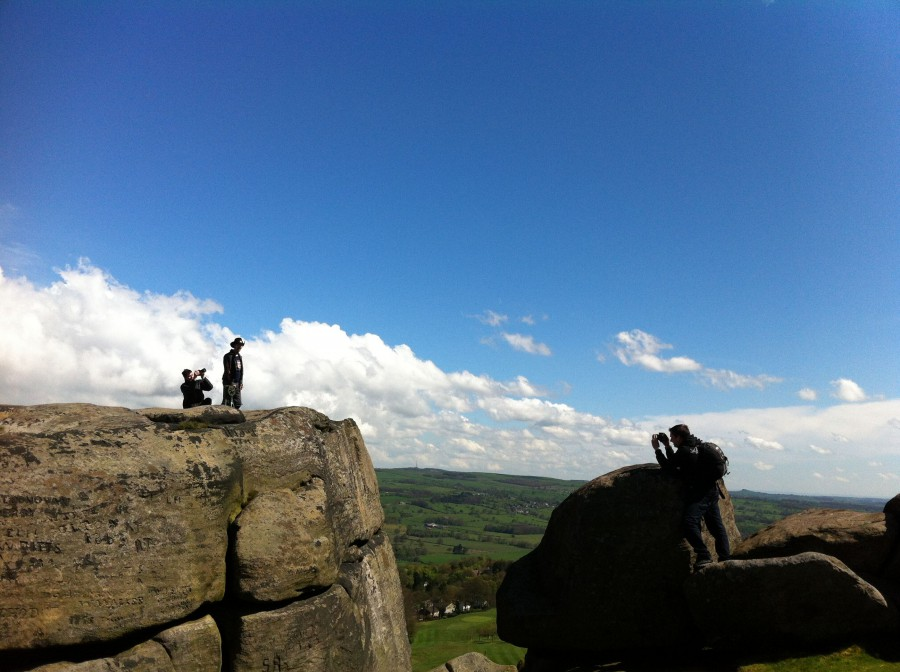 A huge rocky outcrop against a blue sky - two figures can be seen on one rock and another film maker can be seen in the foreground, also shooting