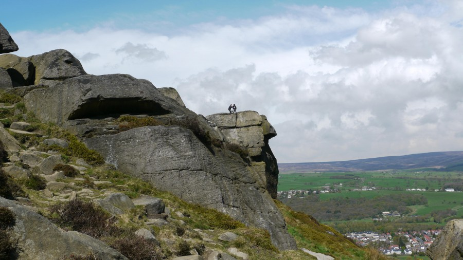 A huge rocky outcrop against a cloudy sky - two tiny figures can be seen - one filming, one in a stetson.