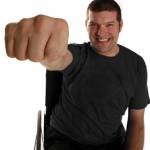 A photo of laurence Clark, is hand and arm raised making a fist towards the camera so his hand appears very big.