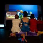 Three performers are watching a screen with their backs to us, they are dressed in circus clothes and are sitting on a fourth performer. The screen they are watching has a playmobil circus on it.