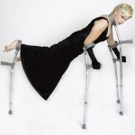 Claire Cunningham balancing on four crutches - two for her arms, one for her legs and one at her neck. She is all in black including with black long gloves.