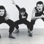 Three white faced mimes, dressed in black, in crouched poses facing the camera