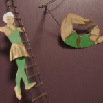 two circus figures - one on a ladder and one on a trapeze - they are made of flat metal and part of a wall hanging