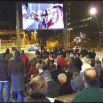 Image of the Plymouth big screen at dusk with a crowd of people gathered to watch the screen showing a band performing.