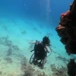 screen shot of Sue Austin diving underwater in her underwater wheelchair.